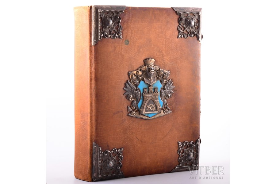 The Photo Album was a gift to the senior foreman of the Guild of Bricklayers of Riga City Vilhelm Donberg on March 13, 1902. It was presented for 50th Anniversary of his tenure as a Head of the Guild. The cover page of the album has an image of the coat of arms of the Riga Guild of Bricklayers. The first sheet with a photo has a floral frame with depicted the coat of arms and views of Riga, which was hand painted with watercolors. Vilhelm Donberg in his work's costume is depicted in the stained glass of the Small Guild building, 1902, Riga, 41 х 34.5 х 10.5 cm, silver cover plates: 84 hallmark, Riga silversmith EB (hallmark N3299a, page 240, М.М.Постникова-Лосева, «Золотое и серебряное дело XV-XXв», М.1995)