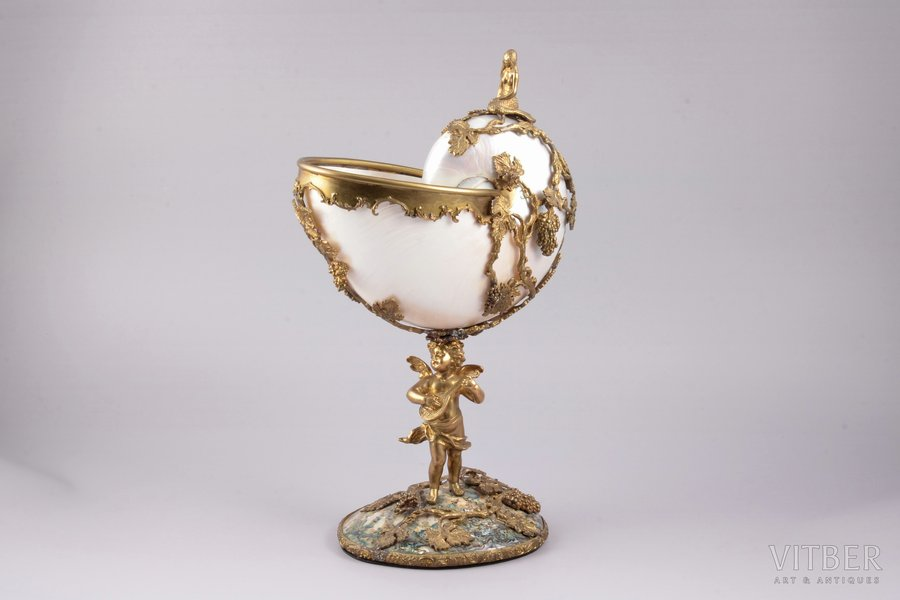 кубок, Nautilus, раковина, бронза, h 31.5 см, вес 1285.3 г., Наутилус существует на нашей планете почти без изменений 450 миллионов лет; это один из немногих моллюсков, выживших со времен динозавров. Наутилус - символ красоты в природе, символ Творения. Раковина Наутилуса символизирует золотое сечение. Золотое сечение широко применяется в искусстве, архитектуре и религиозной символике. Великие художники использовали золотое сечение в картинах. Музей Гугенхейма, спланированный Фрэнком Ллойдом Райтом, имеет форму раковины наутилуса. Со временем люди, очарованные красотой форм и блеском перламутрараковины наутилуса, научились обрабатывать ее и создавать настоящие шедевры ювелирного мастерства.Ювелиры XVI-XVII веков создавали работы, которые использовали как дары и призы высокопоставленным персонам. Обладателькубка из раковины наутилуса выносил его лишь в самых торжественных случаях как символ своего престижа. Ранее считалось, что раковины наутилуса обладают очищающими свойствами. В кубках наутилусах яд теряет свою силу, при этом стенки сосуда изменяют окраску и тускнеют. Именно поэтому кубки Наутилусы стали популярным подарком среди послов, знати и государственных делегаций. Кубки наутилусы дарили в знак открытости, чистоты и доброжелательности намерений своего визита. На Руси такие кубки появились во времена Ивана Грозного. Заморские князья преподносили в дар нашим царям столь значимые и искусно выполненные кубки. Продажа кубков простолюдинам была запрещена. Пить из них могли себе позволить лишь богатые и знатные люди. Кубки из раковин наутилуса подчеркивали богатство и статус человека, их хранили как драгоценный предмет интерьера.