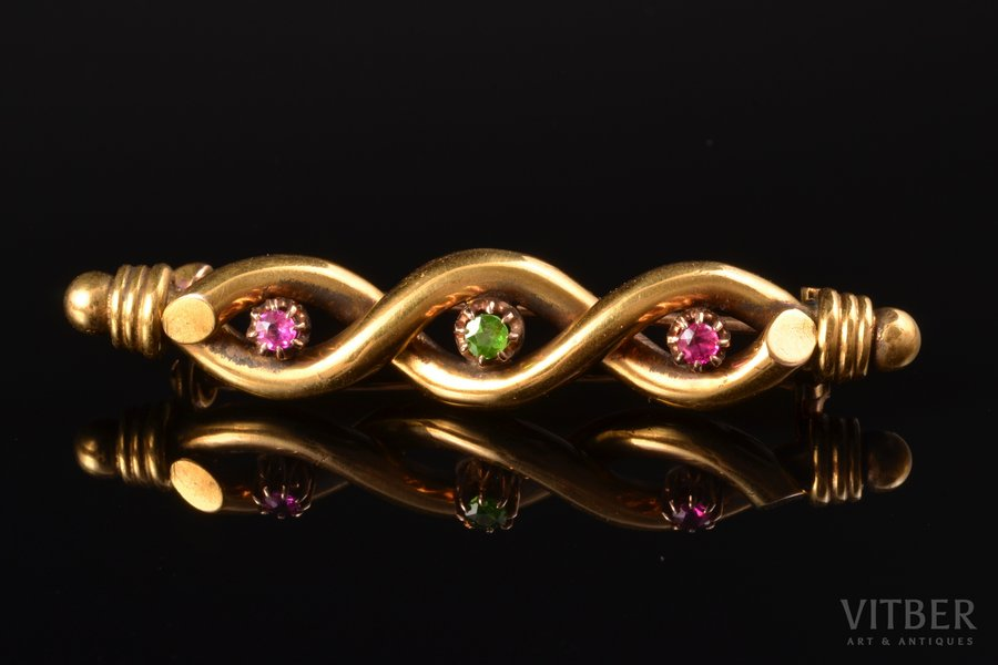 a brooch, gold, 56 ПТ standart, 7.28 g., the item's dimensions 5.5 x 1 cm, emerald, ruby, the end of the 19th century