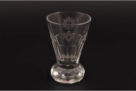 """glāze, brīvmūrniecības simbolika, piederējis LR Ārlietu ministram Vilhelmam Munteram, 20. gs. 1. puse, h 8.6 cm, LR Ārlietu ministrs (1936-1940) Vilhelms Munters 1929. gadā tiek uzņemts Stokholmas brīvmūrnieku ložā """"Den Nordiska Foersta"""". 30-tajos gados Munters pasūta ar roku šūtus apavus pie kurpnieka Auziņa k-ga. Kā pateicību par labo darbu Munters Auziņam uzdāvināja vairakus ar brīvmūrniecību saistītus priekšmetus. 50-tajos gados Auziņa k-ga (miris 1958. g.) sieva strādāja par auklīti Olševsku ģimenē. 2 stikla priešmeti tiek uzdāvināti auklējamam Raimondam Olševskim"""