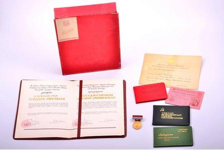 komplekts, uz LPSR Ministru Padomes priekšsēdētāja vietnieka Vladimira Stroganova Grigorija dēla vārda: Latvijas PSR Valsts prēmijas medaļa ar diplomu (1985), PSRS Sarkanā Krusta un Sarkanā Pusmēneša biedrību savienības dalībnieka biļete (1960), ārstēšanās grāmatiņa Nr. 19 (1955), apliecība Trešā Vissavienības kolhoznieku kongresa delegātam (1969), ielūgums uz rikšošanas sacensībām, ielūgums uz Jaunā gada sagaidīšanu no PSRS Ministru Padomes priekšsēdētāja (1955), Latvija, PSRS, 1955-1985 g.