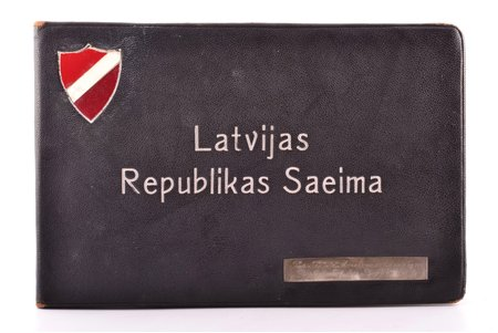 """Latvijas Republikas Saeima"", albums 1. Latvijas Republikas Saeimas deputātu portretiem, ar sudraba plāksni ar veltījumu ""Par K.I.K.A. mērķu veicināšanu Bijušajam Satversmes Sapulces loceklim P. Ašmanim"", 1923, Kara Invalīdu Kulturelās Apvienības izdevums, Riga, 55 pages, leather binding, ex libris, 14.3 x 22.8 cm, coat of arms on the cover is restored; Paul Ashmanis – the Head of the Information Department of the Ministry of Foreign Affairs of the Republic of Latvia from 1919 till 1920. During the absence of Zigfrid Anna Meierovics Paul Ashmanis was the Acting Minister of the Ministry of Foreign Affairs. In the period of 1920-1922 he had been a deputy of the Constitutional Assembly of Latvia, as well as the member of the National Alliance"
