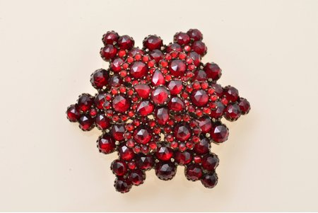 "a brooch, ""Bohemian star"", tombac, 9.76 g., the item's dimensions 3.8 x 4.3 cm, garnet"